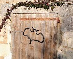 Décoration d'une porte de grange : chauve souris en fers à cheval, the batcave entry ?