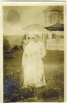 """This previously had the caption """"Ghost Nurse"""". Take a look at the somewhat transparent gazebo and tower in the background. Notice the same gazebo on the right, completely solid. This is a double exposure."""