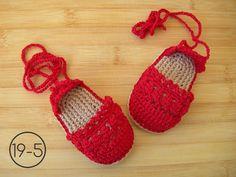 Alpargatas de color rojo hechas a ganchillo con la suela imitando esparto, cordones largos para atar a los tobillos.