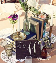 Centerpieces for tables: table numbers, rented books (from Bee Lavish), tall brass candlesticks (from Bee Lavish), flowers from Wild Bunches, and mercury votives