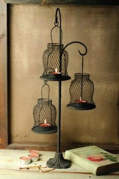 """A trio of flickerfilled wire baskets dangle from an iron tree. 20"""". Tea lights not included."""