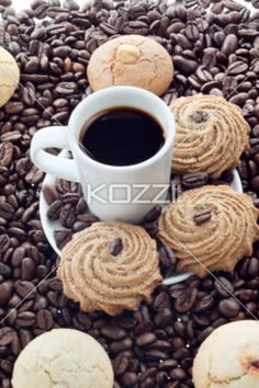 coffee in a mug with sugared cookies - Portrait of coffee in a mug with sugared cookies place in white saucer with lots of coffee beans