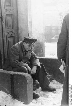 An unusual snapshot of Albert Speer, Munition minister, sitting on doorsteps apparently tired, 22 Dec 1942.
