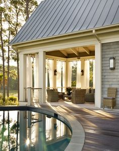 Cottage Home Features A Circular In Ground Pool Next To A Covered Deck  Filled With Wicker Furniture Finished With White Grommet Outdoor Drapes.