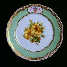 """First Lady Sarah and President James K. Polk's 1846 White House China.  The 9"""" Dessert Service from the set displays Green Border with a Shield Within Gold Borders and Botanically Accurate Flowers in the Center of Each Piece."""