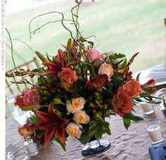 Rustic branches added height to the autumn-colored blooms in the centerpieces
