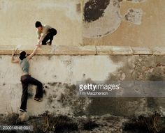 Stock Photo : Young man helping young woman over wall