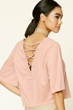 A faux suede top featuring a lace-up back, a V-neckline, short sleeves, and a boxy silhouette.