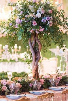 Tall wedding centrepieces on a table decorated with flowers.