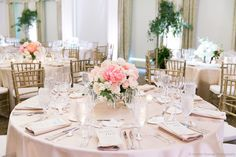 a lush spring time wedding table arrangement of faded coral charm peony, peach juliet garden rose, garden spirit rose, white majolik spray rose, vendela rose, sarhara rose, elm and bay leaf in a classic silver revere bowl, surrounded by votives.