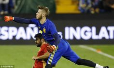 David De Gea (right) leaps over striker Diego Costa to punch a ball away in Spain training