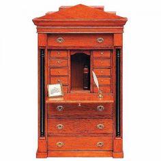 Biedermeier Schreibsekretär (40095). Bausatz aus unbehandelten Naturholz, veredelt mit unserem Kirschbaum Flüssigwachs (43004). Der Sekretär hat 4 große Schubladen, 10 kleine Schubladen und eine einschiebbare Arbeitsplatte. Das abgebildete Tintenfaß (17800), mit echter Feder, sowie das antiquarische Buch (19370) gehört nicht zum Lieferumfang.