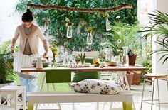 Tavolo in legno con piatti, bicchieri, piante e fiori. Panca NORNÄS in legno trattata con vernice bianca e verde, con cuscino a fiori.