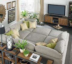 Huge gray Bassett Beckham Pit Sectional sofa, green pillows, industrial bookshelves, subway sign, wood sunburst mirror, exposed brick wall painted white and industrial media cabinet.