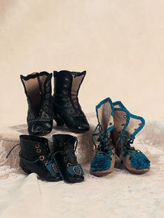 "Three Pairs of French Huret-Style Boots Sized for 16""-17"" poupee (40-43 cm). Including high linen boots with blue banding,hand-edged grommets with laces,blue silk rosettes,wooden heels,tan soles with darker tan edging; black leather boots with blue uppers,hand-stitched grommet holes,wooden heels,no laces,tan soles with darker outer edges,impressed with square; and black leather ankle boots with brass grommet holes,laces,blue rosettes with brass medallions. Circa 1865 On girlswood.com"