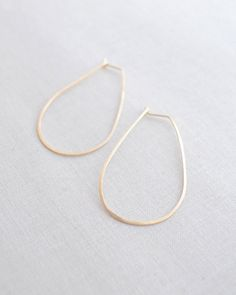 Large Hammered Gold Hoop earrings by Olive Yew. Slight teardrop shape. Also in silver. From $40.