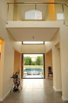 vista desde el hall en doble altura: Pasillos, vestíbulos y escaleras de estilo  por Parrado Arquitectura