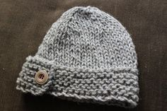 hand knitted baby hat with button. pattern courtesy of blueberrybarn
