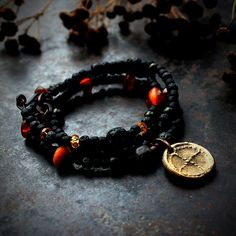 Black wrap bracelet or necklace with a sun symbol charm, solar wheel, and Baltic amber