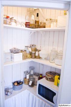 Skafferi i lantligt kök. Skafferiet har fått sig en massa fina burkar istället för originalförpackningar!