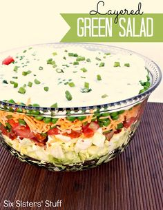 LAYERED GREEN SALAD (serves 8-10) 1 head iceberg lettuce,  2 C baby spinach,  salt and pepper,  10 hard boiled eggs,  1 (12 oz) pkg bacon,  4 tomatoes,  1 bunch green onions,  1 C cheddar cheese,  1 (10 oz) bag frozen peas,  DRESSING: 1/2 C mayonnaise,  1/2 C sour cream,  2 T sugar