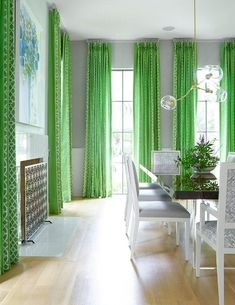 Resplendent gray and green dining room boasts tall steel framed windows framed by gray wallpapered walls lined with wainscoting and dressed in green french pleated trellis curtains while on an adjacent wall, a white marble fireplace is flanked by windows and accented with a blue painting mounted above it.