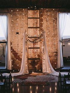 Backdrop med ljusslingor i en bröllopslokal med tegelvägg och högt tak.