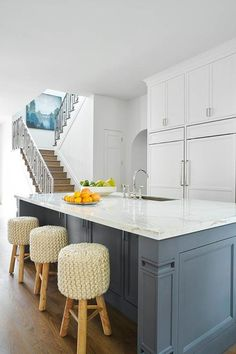 A slate blue kitchen island is topped with white quartz fitted with a sink and deck-mount faucet lined with round knitted bar stools.
