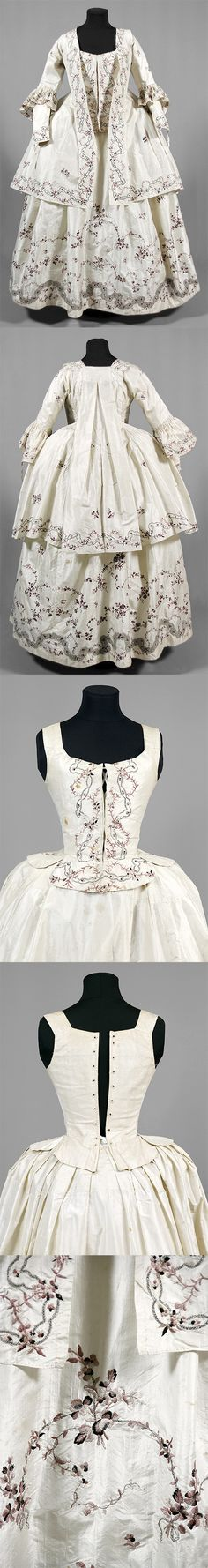 """Gown of white silk, 1770, Sweden, embroidered with darker and lighter purple silk and silver. Consists of seven parts, skirt (width 284 cm), bodice (2 parts), jacket with watteau pleat in the back, 2 loose sleeves and headpiece. Belonged to """"Aunt Ulla"""" Ulrica Christina Cronstedt (1756 - 1841) on Gärdesta. Sörmlands museum"""