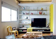 Um dos quatro quartos, aberto para a sala, abriga o home theater, com móvel e estante criados pelo SuperLimão. A mesa de centro é de paletes que embalavam a geladeira