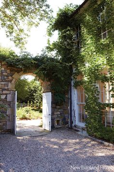 arched stone entry, gravel courtyard