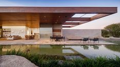 Glass walls lining the social areas of this house slide and fold away to create an entirely open-air space overlooking a pool and the adjacent golf course