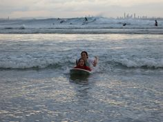 3 Year Old Girl Surfing With Mom In Rainbow Bay Australia.