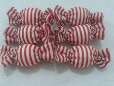 Laços em formato de bala, confeccionados com tecido em algodão e acabamento com elástico resistente e enfeite de flor em biscuit.. Medi aproximadamente 4 cm. Embalagem com 10 unid.