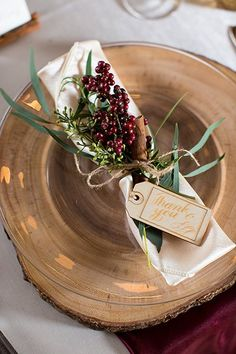 A wooden slab placemat and napkin tied with twine, berries, and cinnamon stick is full of rustic charm.