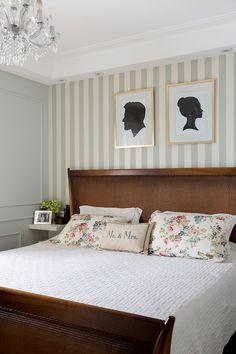 Decoração de apartamento com quarto de casal com revestimento de listras, cama de madeira e adornos.