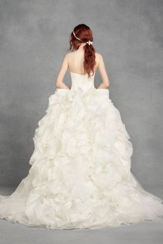 Make a style statement in this modern-chic gown from White by Vera Wang. This gown, made for the bold, individualist bride, features a ruffled tulle skirt accented with organza rosettes atop a swagged