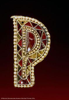 """Pieza de orfebrería """"polícroma"""" cloissoné perteneciente a una espada o """"protosable"""" recto con doble suspensión de los siglos V-VI. Se ha supuesto que la forma de P alargada de estas preciosas guarniciones metálicas de las vainas recuerde la deformación sufrida, a causa del peso del arma, por las sujecciones de cuero de las vainas menos lujosas de las espadas comunes."""