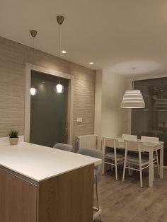 Cocina con barra en península realizada en solid surface. Revestimiento de pared en porcelánico efecto cemento rayado. Iluminación decorativa en cristal y tela. Puerta corredera en cristal templado. Proyecto diseñado y desarrollado por AZ diseño.