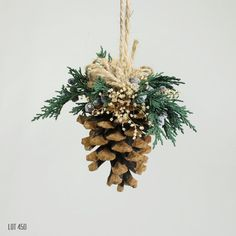 Pine cone Christmas tree ornament, with preserved juniper pine and babys breath with a twine bow and hanging loop. Could also be used as a pomander for a bride or wedding decor. Approximately 3 1/2 x 2 Rustic woodland holiday style Preserved evergreens Preserved babys breath Long lasting Coordinating decor in my shop: 10 wreath: www.etsy.com/listing/469659295 Little 5 wreath: www.etsy.com/listing/469612295 Cake topper: www.etsy.com/listing/469828337