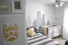 To+create+a+space+that+is+both+nursery+and+guest+bedroom,+a+twin+bed+was+brought+in+to+accommodate+the+baby's+mother+or+other+guests+at+night.+The+gray+and+white+striped+bedspread+complements+the+neutral+color+palette+of+this+travel+themed+nursery,+while+the+gold+and+silver+mobile+and+wall+decal+match+the+gold+chevron+throw+pillow+that+adorns+the+guest+bed.+