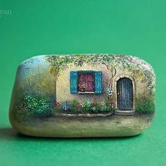 House with Aqua door& window painted on a rock.