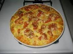 Saltea las cebollas y el ajo en aceite hasta que estén ligeramente doradas. Extiéndelas en la parte inferior de una bandeja para quiche. Cubre con el queso. Cubre con la albahaca. Mezcla la crema, el agua, la sal, la pimienta y los huevos; bate bien. Acomoda las rodajas de tomate sobre el queso. Cub…