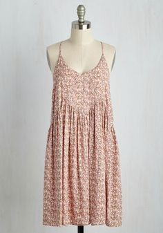 Greet the weekend with a hot cup of coffee and a cool new style - this pretty, blush pink shift dress! With a diamond-shaped bodice boasting eyeleted trim, a gathered skirt, and a petite print of white, blue, and green blossoms, this racerback dress forms a flowy silhouette that amplifies your early morning glow.