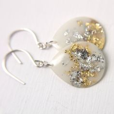 white drop earrings with silver and gold leaf on by tinygalaxies