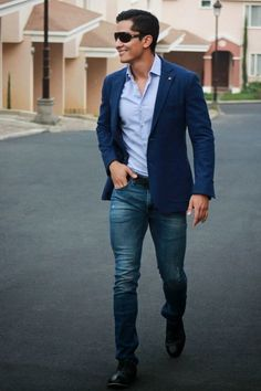 Pairing a navy blazer jacket with navy jeans is an on-point option for a day in the office. For footwear go down the classic route with black leather oxford shoes. Shop this look on Lookastic: https://lookastic.com/men/looks/blazer-long-sleeve-shirt-jeans/17616 — Light Blue Long Sleeve Shirt — Navy Blazer — Navy Jeans — Black Leather Oxford Shoes — Black Leather Belt — Black Sunglasses