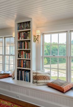 Long window seat with built-in bookshelves via Crisp Architects