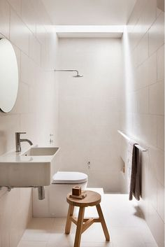 White bathroom with single wood stool