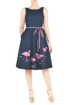 Pink flamingo embroidery patterns the ruched pleat skirt of our feminine poplin dress paired with a contrast, waist-defining tie-belt.