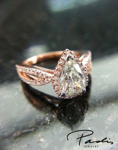 Customized rose gold engagement ring with pear shaped center diamond.